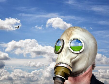 Man in gas mask against blue sky photo
