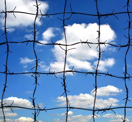 barbwire: Barbed wire against blue sky Stock Photo