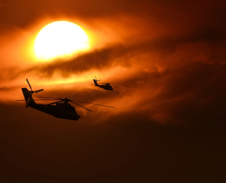 against the sun: Military helicopters silhouette flying against sun