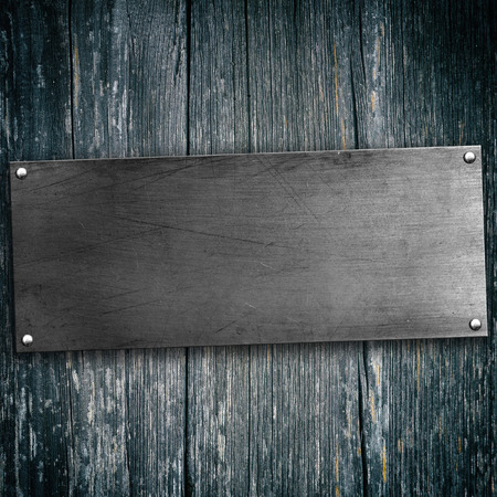 antique background: Metal plate with rivets on wood background