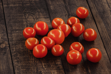 tasty cherry tomatoes on a wooden stand, wooden background. Stock Photo