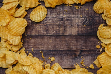 crispy potato chips on wooden background. chips started.