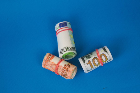 bundles of twisted money of different currencies on a blue background.