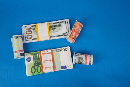 several wads of money of different currencies on a blue background