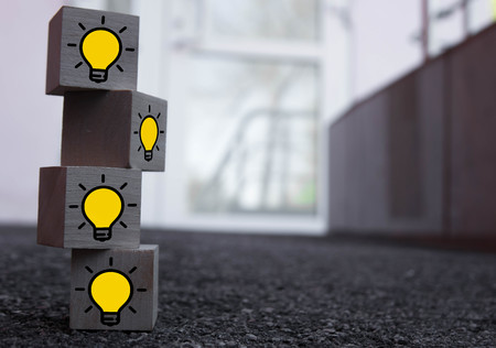 4 wooden cubes with a pattern of a yellow burning lamp on top of each other on asphalt. Stok Fotoğraf