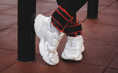 man stands in white sneakers on a rubber pad