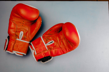red faded boxing gloves on blue background.