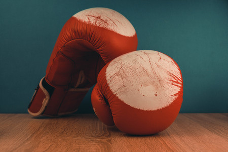 red boxing gloves on blue wooden background.