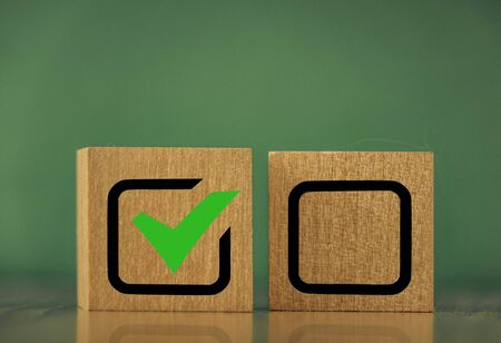 wooden cubes with the image of check marks marks on a green background