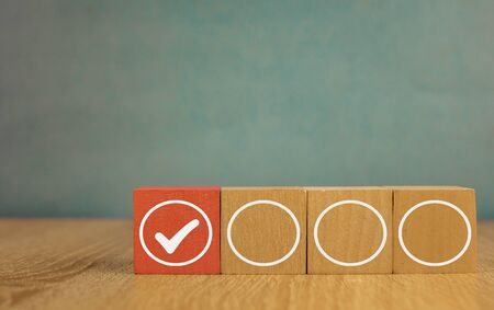 wooden cubes with and tick accomplished goal and white circles on a blue background.