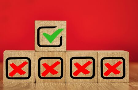 Wooden cubes with drawn marks on the red background.