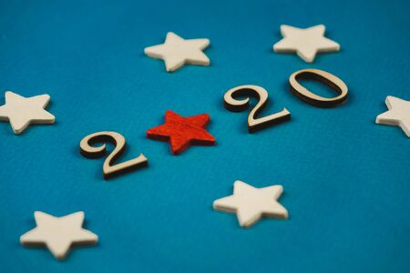 2020 number from wooden numbers on a blue background with scattered stars gears and flags around.