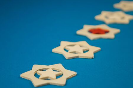 five wooden stars and one of them is red on a blue background.