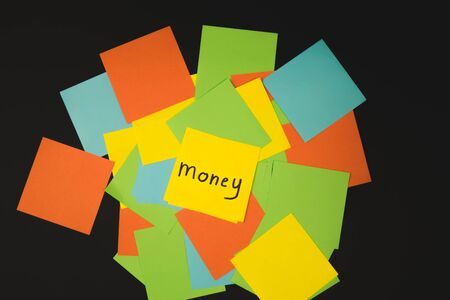 the word money on a piece of yellow paper among multicolored paper. Imagens