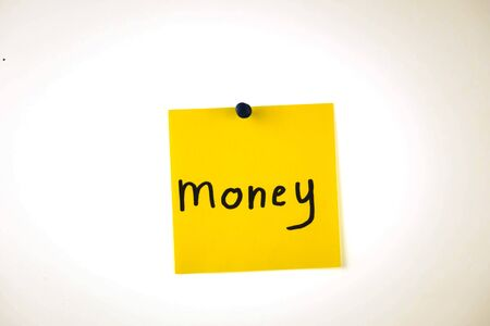 the word money on a piece of yellow paper among multicolored paper. Stock Photo