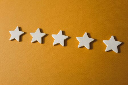 five white stars on an orange background.