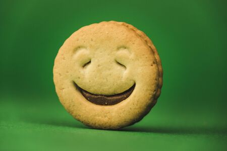 smiling cookies and different emotions on a green background.