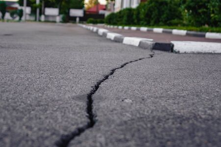 a long crack on asphalt leading to the curb.