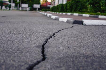 een lange scheur op asfalt die naar de stoeprand leidt.