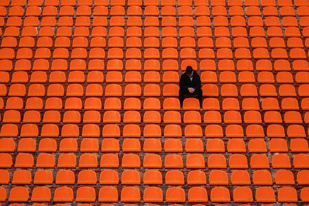 homme seul sur le siège vide du stade acclamant l'équipe, concept d'armée d'un seul homme.