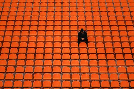 lonely man on the empty stadium seat cheering for the team, one man army concept.