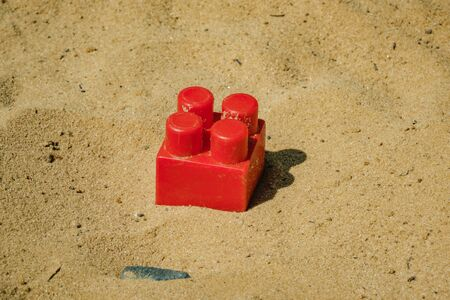 part of the children's designer red lying on the sand Archivio Fotografico