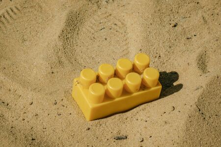 part of the children's designer yellow lying on the sand.