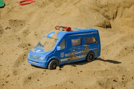 toy police truck lying in the sand Stock Photo