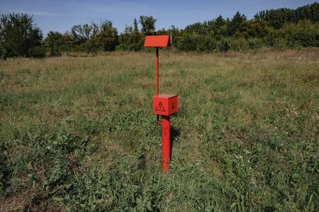 red electric cable stands in the field