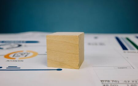 template in the form of a wooden cube lying on a stack of documents on a blue background.