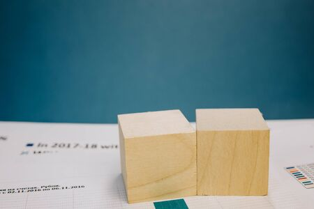 template in the form of two wooden cubes lying on a bundle of documents on a blue background.