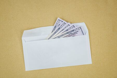 Stack of dollars in open envelope on brown background. Concept of corruption, illegal profit, racketeering. Zdjęcie Seryjne