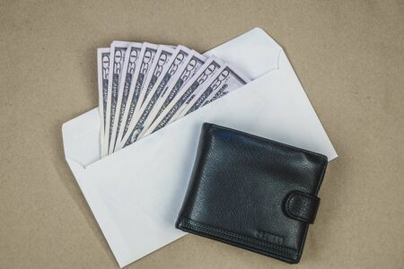 Stack of dollars in the open envelope next to the black purse on brown background. Concept of corruption