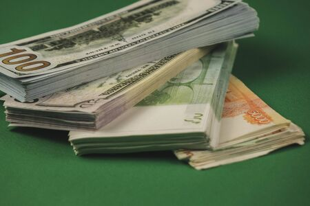 several wads of cash lying on top of each other on a green background.