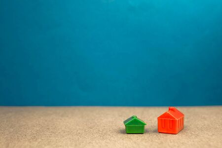two miniature houses red and green on a blue background.