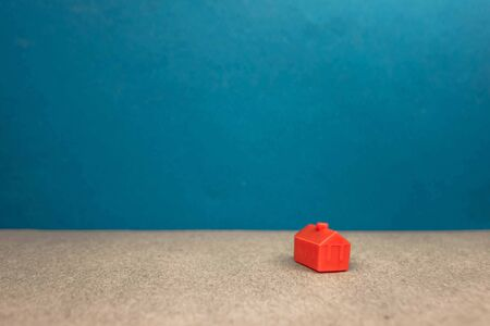 red miniature house standing alone on a blue background, the concept of wealth, success