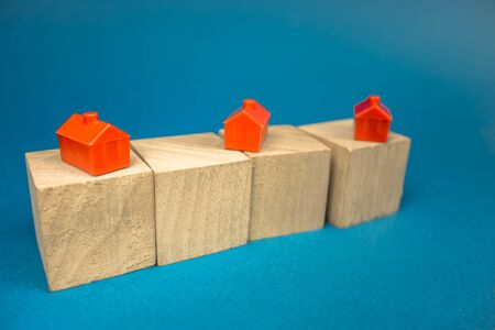 red houses standing on wooden cubes on a blue background