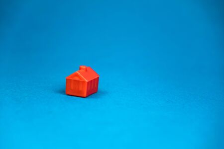 red miniature lonely house standing on a blue background