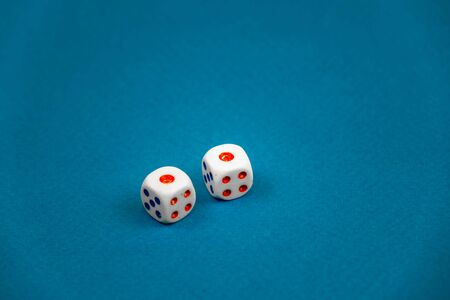 two white dice isolated on a blue background
