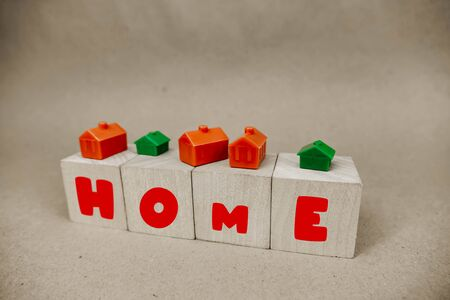 the inscription home on wooden cubes among the red and green houses Stok Fotoğraf