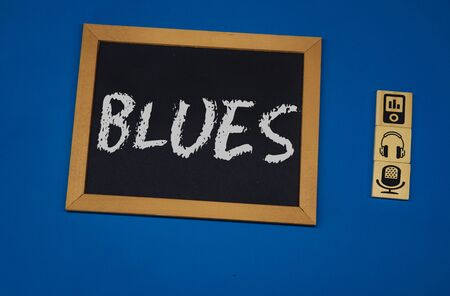 inscription BLUES on a black board with a blue background with three wooden cubes