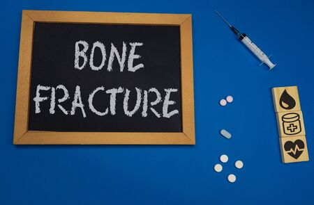 wooden tablet on blue medical table with the word bone fracture