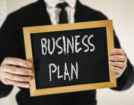 male businessman in a suit with tie holds in his hand a sign with the inscription BUSINESS PLAN