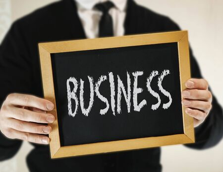 male businessman in a suit with tie holds in his hand a sign with the inscription BUSINESS
