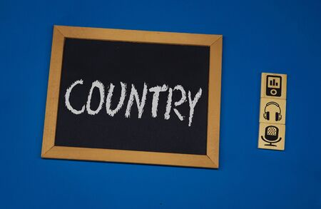 inscription COUNTRY on a black board with a blue background with three wooden cubes