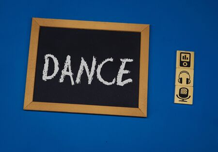 inscription DANCE on a black board with a blue background with three wooden cubes