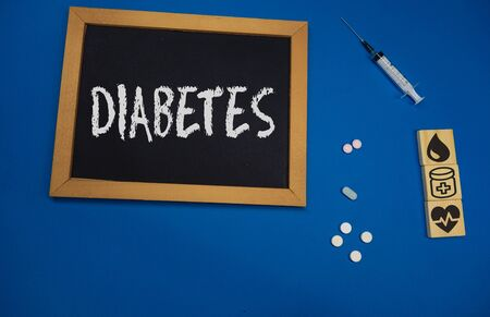wooden tablet on blue medical table with the word DIABETES