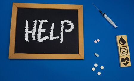 wooden tablet on blue medical table with the word HELP