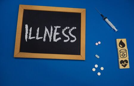 wooden tablet on blue medical table with the word ILLNESS