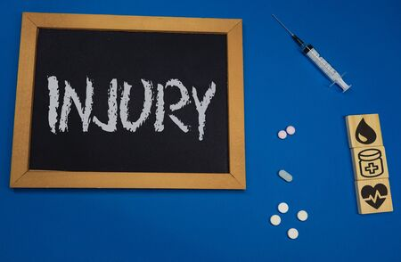 wooden tablet on blue medical table with the word INJURY